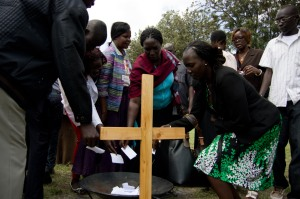 Participants in the Trauma healing groups write down their pain (using words, pictures, or symbols) on pieces of paper then take them to the cross.