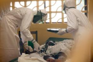 Dr. Kent Brantly, left, treats an Ebola patient